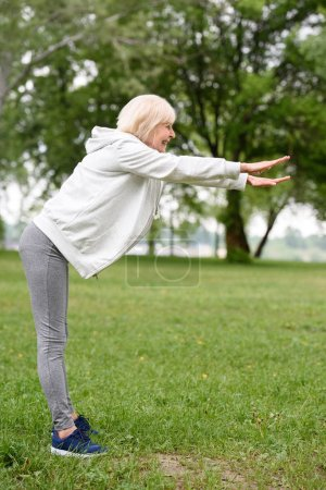 elderly sportswoman exercising on green grass in park, healthy lifestyle