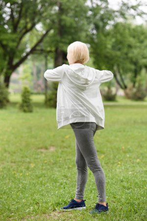 back view of senior sportive woman exercising on green lawn in park