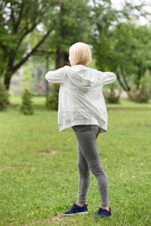 vue arrière du senior femme sportive exerce sur la pelouse dans le parc