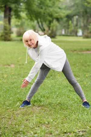 senior athletic woman in sportswear training on green lawn in park