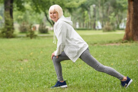 smiling elderly sportswoman training and doing lunges on green lawn in park