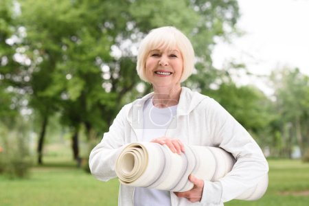 cheerful senior woman with yoga mat in park