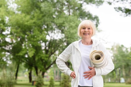 cheerful elderly woman holding yoga mat in park