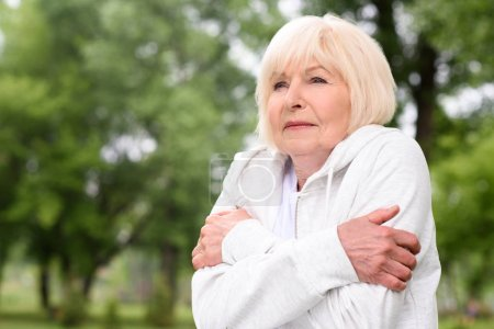 senior woman with grey hair frozen in park