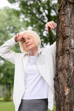 senior tired woman resting near tree in park
