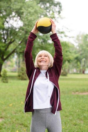 Photo pour Personnes âgée sportive avec médecine-ball dans parc de verdure - image libre de droit