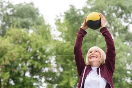senior sportswoman exercising with medicine ball in park