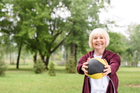 senior sportswoman training with medicine ball in park