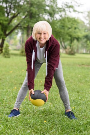 senior woman training with medicine ball in park