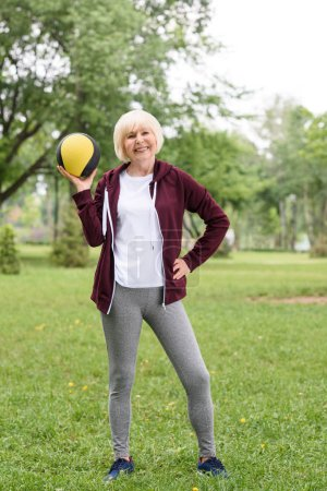 cheerful senior sportswoman posing with medicine ball in park