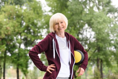 smiling senior sportswoman standing with medicine ball in park