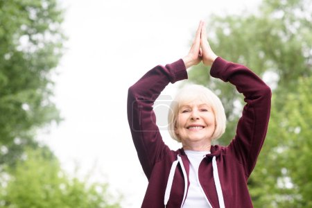 smiling senior woman practicing yoga in park