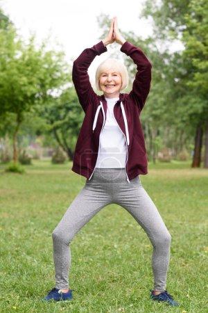 senior woman practicing yoga on green lawn