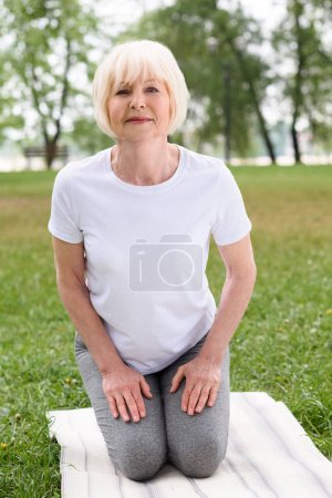 senior woman practicing yoga on mat on green lawn