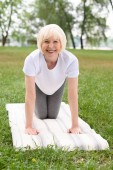 smiling elderly woman practicing yoga on mat on green lawn