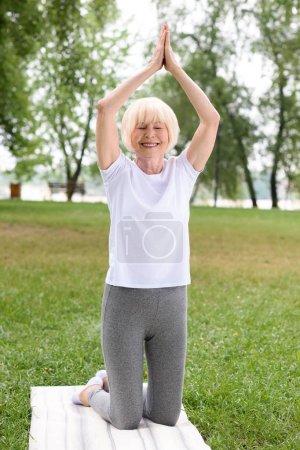 femme senior avec namaste geste pratiquer l'yoga sur tapis dans le parc