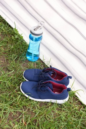 sneakers and sport bottle standing near yoga mat on green grass