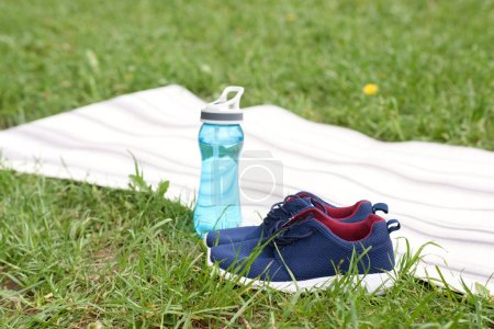 blue sneakers and water in sport bottle standing near yoga mat on green lawn