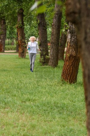 elderly sportswoman running on green grass in park