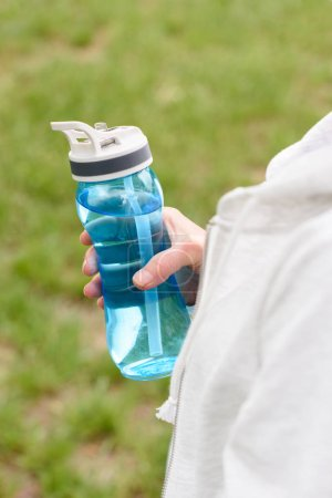 cropped view of woman holding blue sport bottle of water