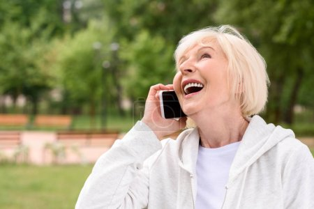 Photo for Laughing elderly woman talking on smartphone - Royalty Free Image