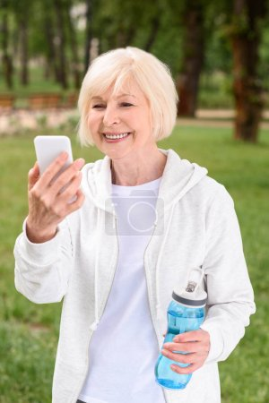 senior woman with sport bottle of water using smartphone