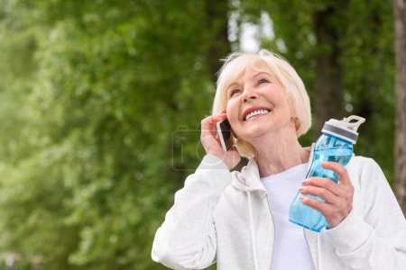smiling senior woman with sport bottle of water talking on smartphone