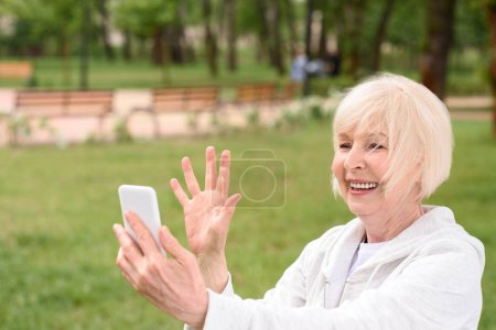 senior woman making video call or taking selfie on smartphone