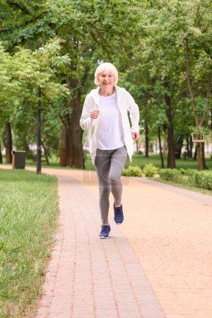 smiling senior sportswoman running in park