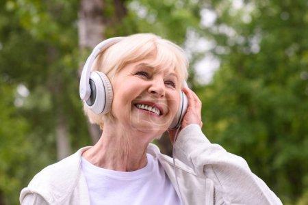 smiling senior sportswoman listening music with headphones in park
