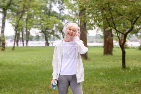 senior sportswoman with sport bottle listening music with headphones in park