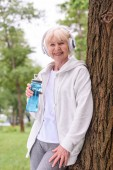 smiling senior sportswoman with sport bottle listening music with headphones in park