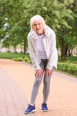 elderly sportswoman with knee pain standing in park
