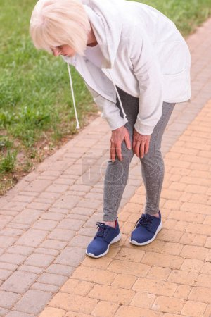 senior sportswoman with knee pain standing in park
