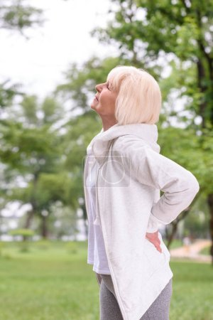 caucasian elderly sportswoman with back ache standing in park