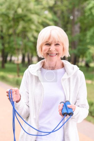 smiling senior sportswoman with skipping rope in park