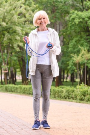cheerful elderly sportswoman standing with jump rope in park