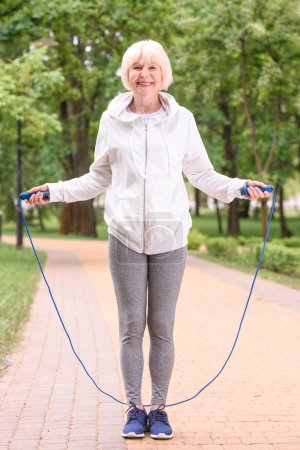 senior sportswoman training with jump rope in park