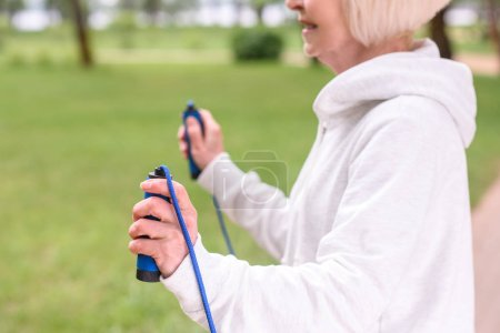 cropped view of elderly sportswoman exercising with skipping rope in park