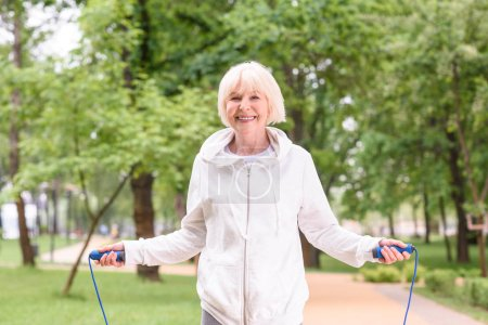 smiling elderly sportswoman with jump rope in park