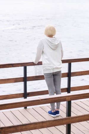 back view of senior woman standing near railings on wooden path near river