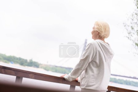 woman standing at wooden railings near river
