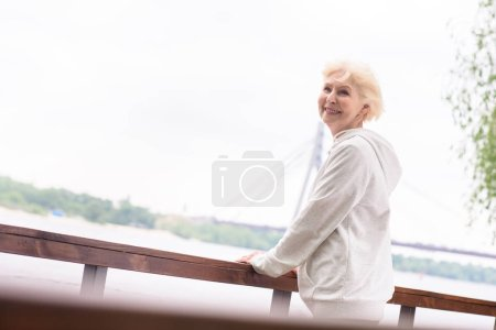 smiling elderly woman standing near wooden railings in park