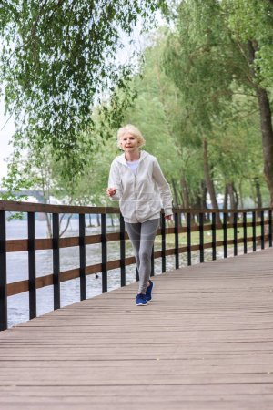 senior sportswoman running on wooden path in park