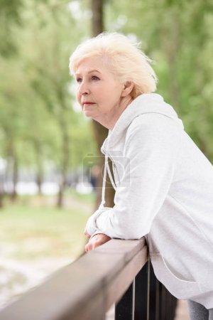 elderly woman standing near railings in park