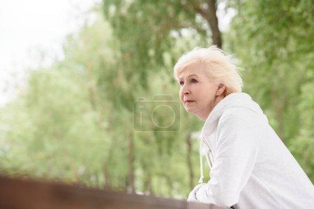 senior woman standing near railings in park