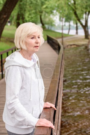 lonely senior woman standing near railings in park