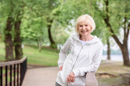 smiling senior woman standing near railings in park