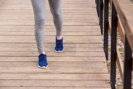 cropped view of sportswoman in sneakers walking on wooden path