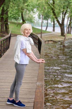 happy senior sportswoman standing on wooden path near railings in park